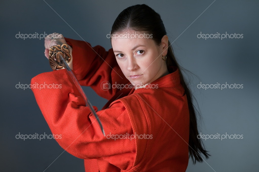 A young girl in a red kimono with a samurai sword  Stock Photo #4853508