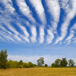 Striped clouds over the cleaned wheaten field — Stock Photo #5354888