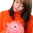 Stock Photo: Young womstanding with piggy bank