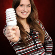 Woman holding an fluorescent light bulb - Stock Photo