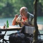 Senior man eat desser at outdoor restaurant — Stock Photo