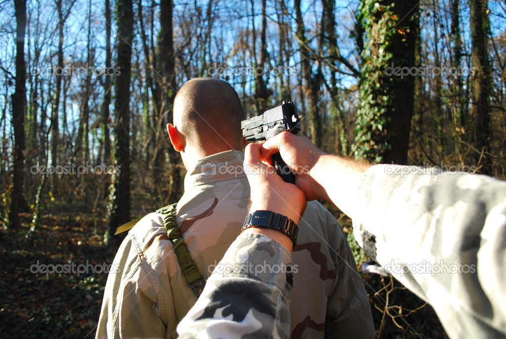 Kidnapper holding a gun to the head of a soldier in a forest — Stock Photo #4252782