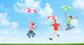 Jumping with umbrellas — Stock Photo