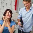 Young smiling couple drink red wine in modern kitchen — Stock Photo #4896177