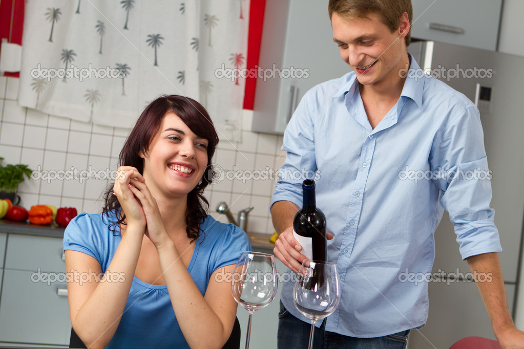 Happy young couple with red wine at home — Stock Photo #4896177