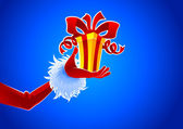 Santa hand with gift — Vector de stock