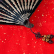 Chinese bamboo fan on red — Stock Photo