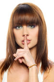 Secret - Young girl with her finger over her mouth — Stock Photo
