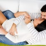 couple heureux portant sur canapé — Photo