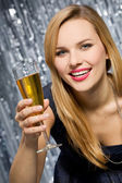 Smiling woman with glass of champagne — Stockfoto