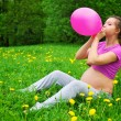 Beautiful pregnant woman blowing balloon — Stock Photo