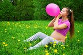 Beautiful pregnant woman blowing balloon — Stock Photo