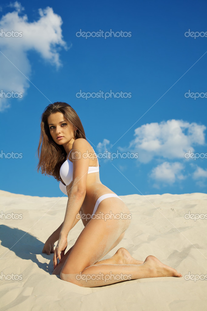 Beautiful young woman in swimsuit posing on sand — Stock Photo #4276133