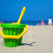 Plastic spade and bucket in sand — Stock Photo #5355786