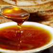 Foto Stock: Tablespoons of honey on the background of pancakes