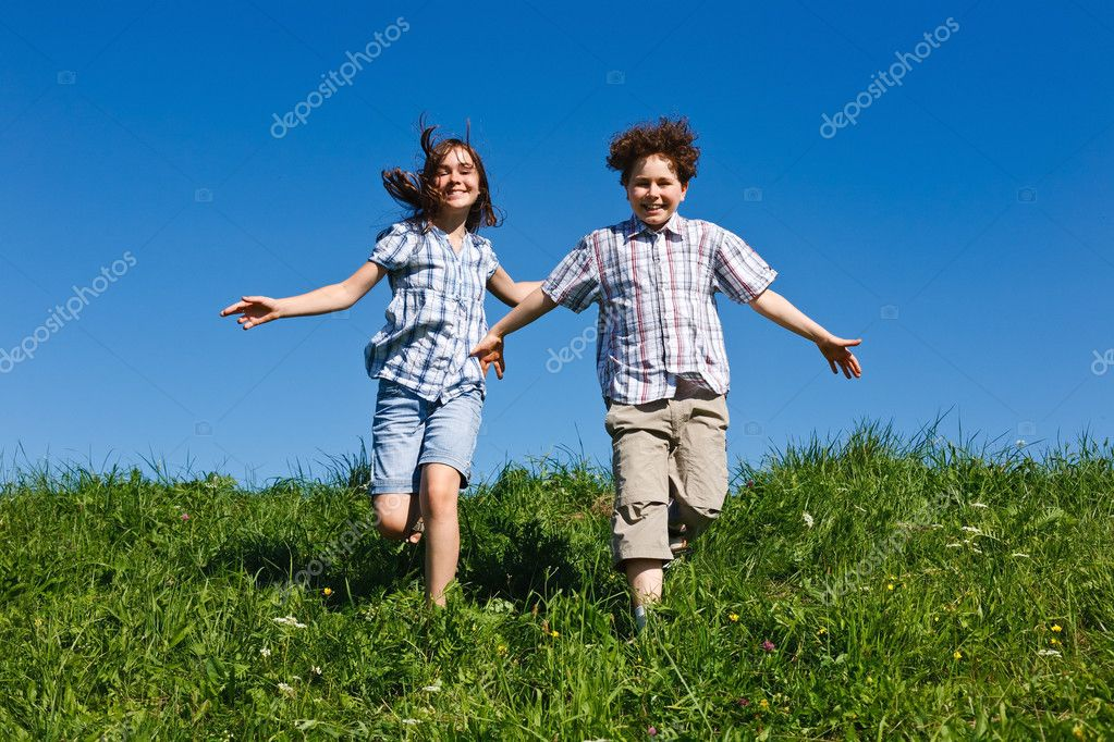 Girl and boy jumping, running against blue sky — Stock Photo #4643323