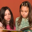 Girls reading book in classroom - Stock Photo