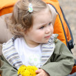 Stock Photo: Girl with flower in pram