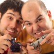 Two young men playing video game console controller - Stock Photo