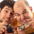 Stock Photo: Two young men playing video game console controller