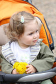 Girl with flower in a pram — Stock Photo