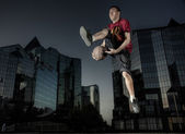 The basketball player in a city — Stock Photo