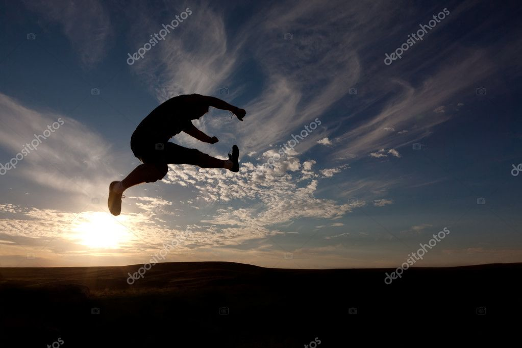 The silhouette of the guy against a decline, the beautiful sky, jumps upwards, a kick — Stock Photo #4624119