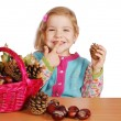 Little girl fun with pine-cone and chestnut — Stock Photo