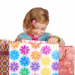 Little girl looking in shopping bags — Stock Photo