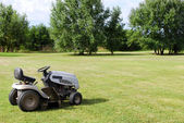 Lawn mower on field — Stock Photo