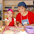 Stock Photo: Mother and daughter making rolls