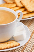 A cup of coffee with a lump sugar and crackers for breakfast — Stock Photo