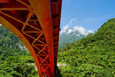 Red bridge across mountains — Stock Photo