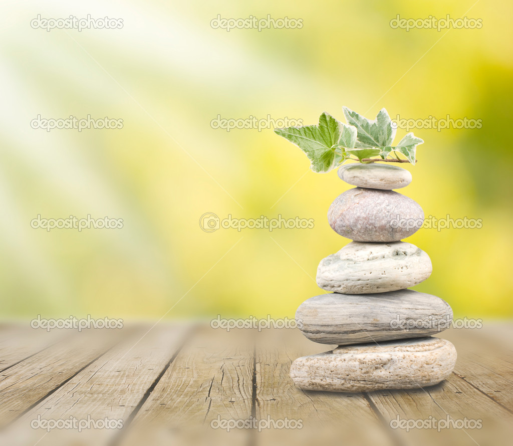 Stack pebbles on wooden table under sunshine — Stock Photo #4005583