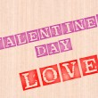 Stock Photo: Valentins day and love word stamped on wooden background.