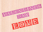 Valentins day and love word stamped on wooden background. — Stock Photo