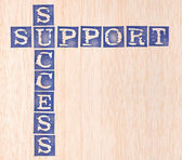 Success and support word stamped on wooden background — Stock Photo