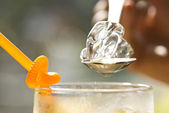 Spoon up sparkling ice cube by hand — Stok fotoğraf