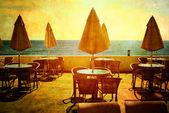 Coffee table and umbrella in the seashore — Stock Photo