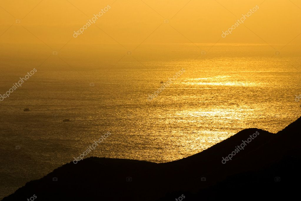 Golden sunshine on the sea where fish boats is going through. The sea with light fog in distant  Stock Photo #5196684