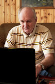 Senior man is working on laptop in living-room — Stock Photo