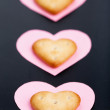 Three crackers on pink paper hearts — Stock Photo