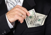 Business man putting dollas into his pocket — Stock Photo