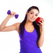 Girl with a dumbbell and an apple — Stock Photo #4219073
