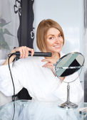 Woman using a hair straightener — Stock Photo