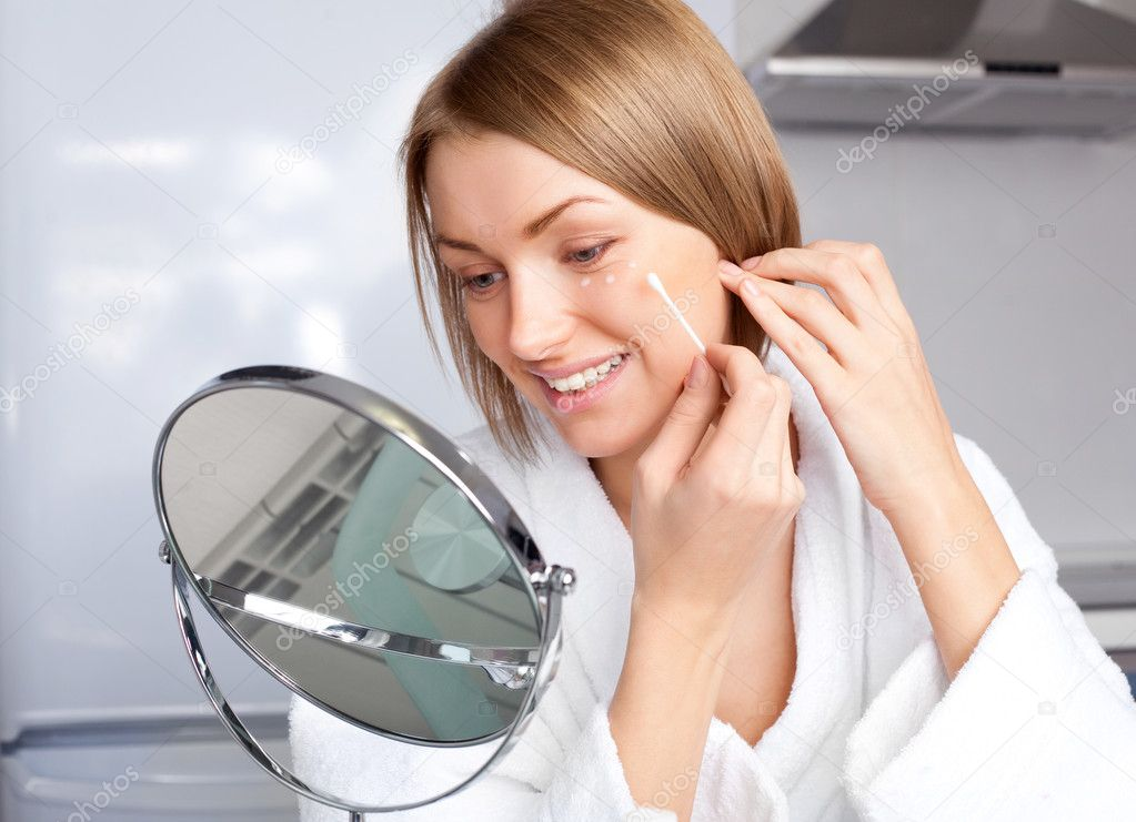 Beautiful young woman applying cream on her face at home  Stock Photo #4219610