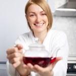 Woman drinking tea (focus of the woman) — Stock Photo
