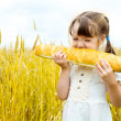 Girl eating a long loaf — Stock Photo