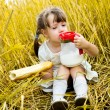 Girl eating a long loaf — Stock Photo #4313489