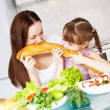 Mother and daughter eat bread — Stok fotoğraf